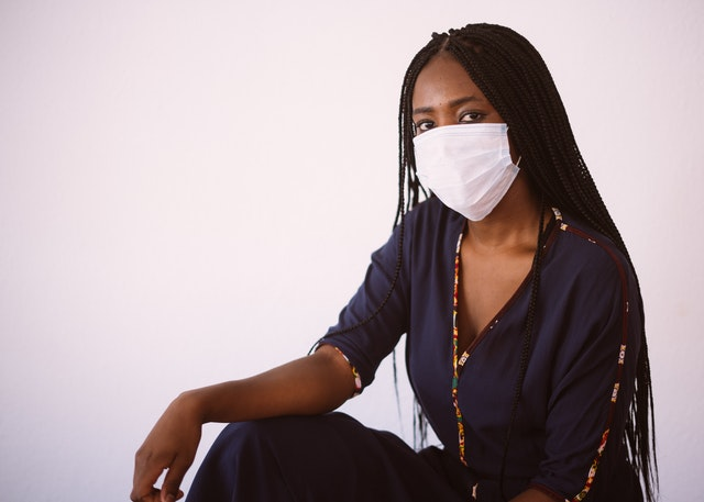 An african american woman putting on face mask