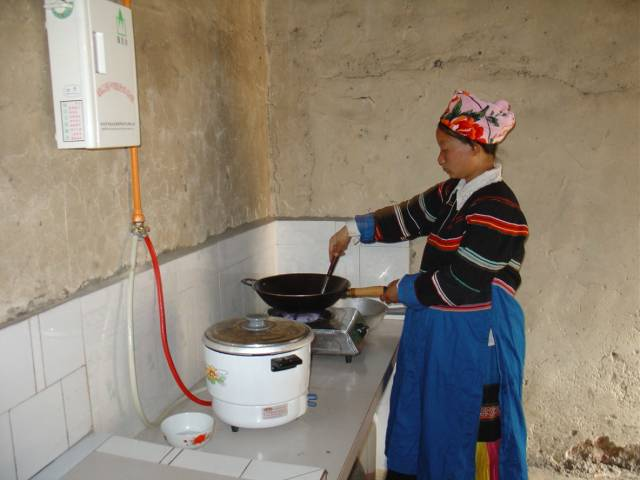 A woman using a biogas stove from a carbon offsetting project