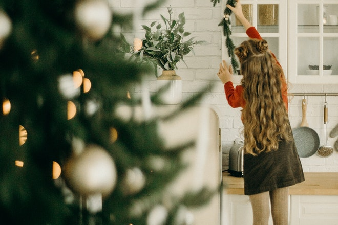 A girl putting up her Christmas decorations