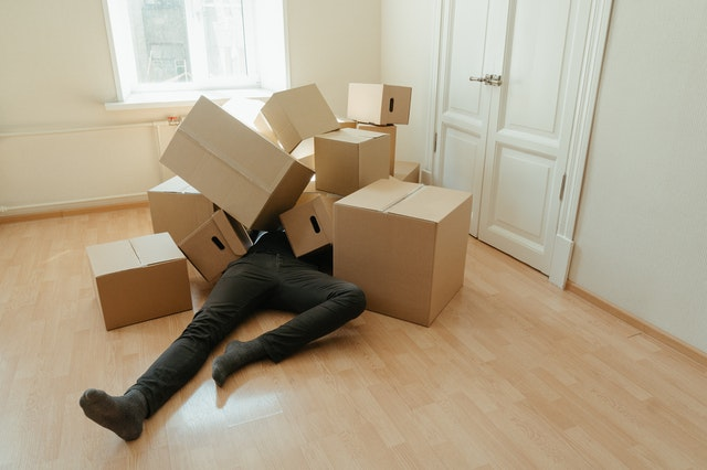 Man lying in brown cardboard boxes which can be a good eco-friendly gift wrapper.