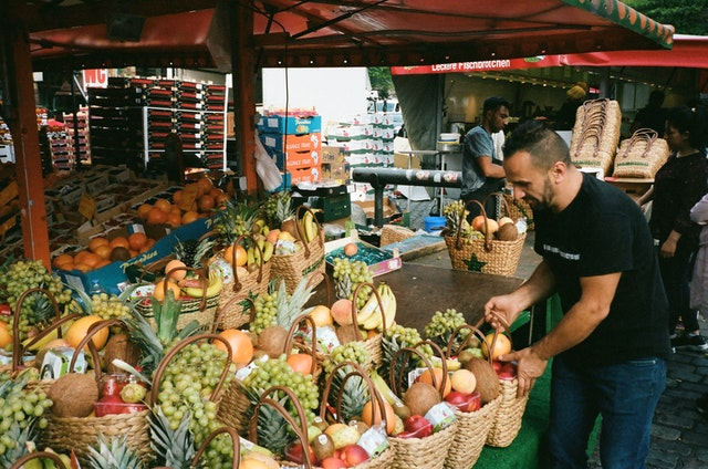A man with fruit baskets in a market