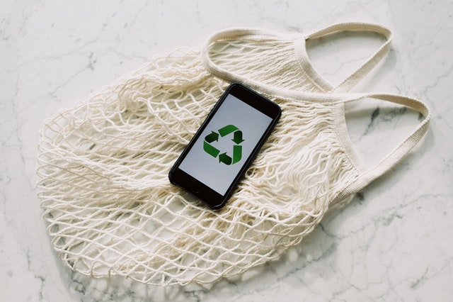 Phone with recycling sign on a reusable mesh bag